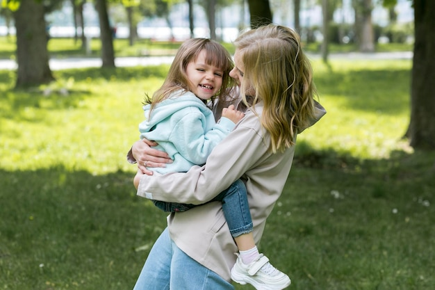 Youngster outdoors and mom hugging
