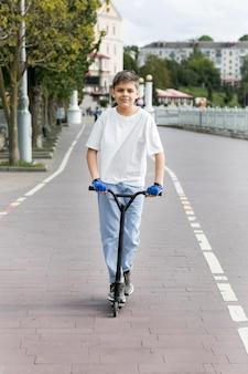 スクーターの正面に屋外の若者