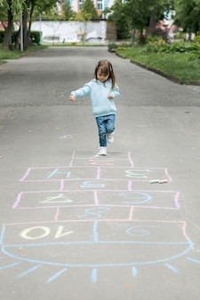 Youngster outdoors playing hopscotch