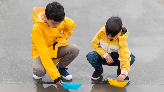 Youngsters in raincoats playing with plastic boats long shot