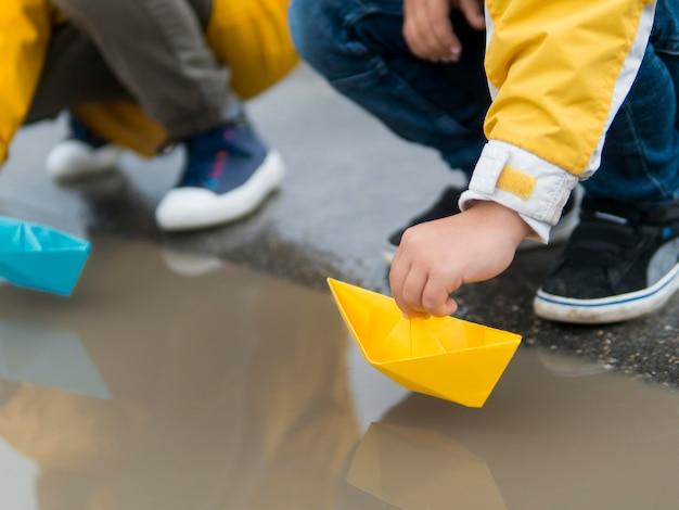 Giovani in impermeabili che giocano con le barche di plastica