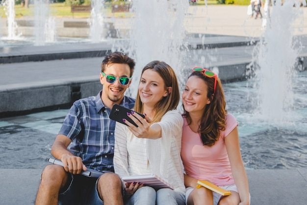 Youngsters with textbooks taking selfie