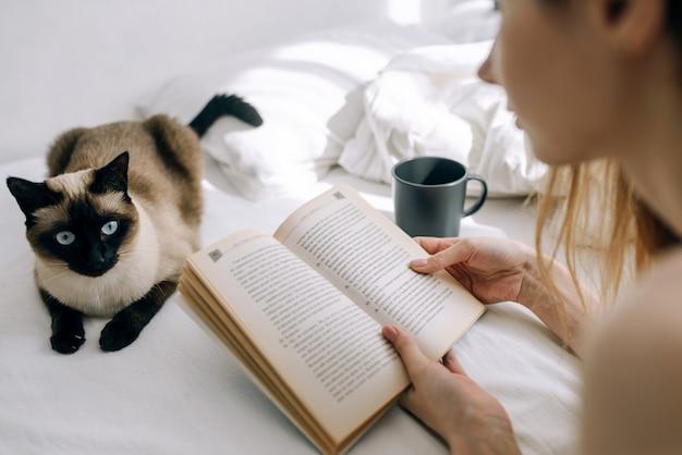 Youngyoung 소녀는 고양이 옆에 밝은 침실에서 침대에서 책을 읽고 커피 한 잔 소녀는 고양이와 커피 한잔 옆에 밝은 침실에서 침대에서 책을 읽고