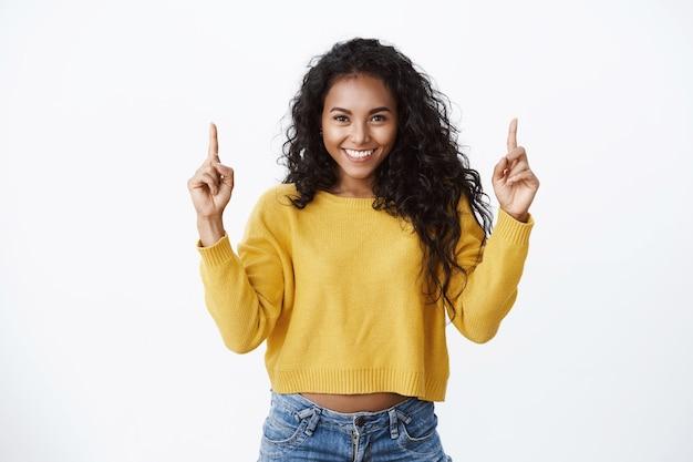 La tua pubblicità quassù. allegra attraente incoraggiata giovane donna afro-americana con acconciatura riccia, indossa un maglione giallo sorridente fiducioso, rivolto verso l'alto, promuove lo spazio della copia superiore