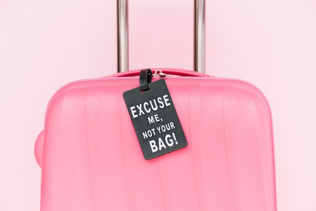 Not your bag tag on pink travel suitcase against pink background