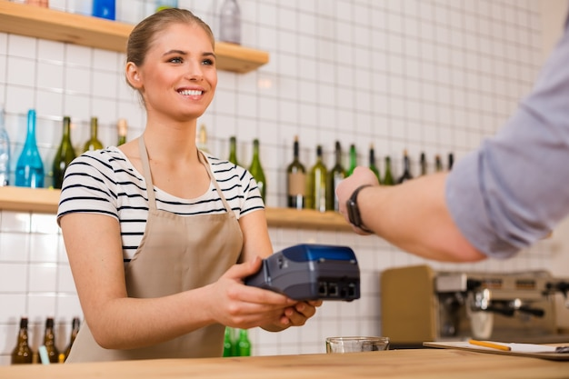 Your card please. cheerful positive young woman holding a credit card terminal and looking at her client while asking for his card