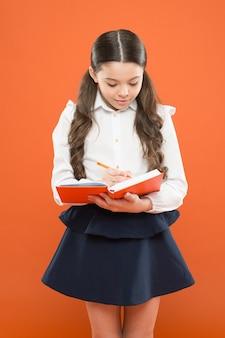 Здесь начинается ваш карьерный путь. напишите сочинение или заметки. вдохновение для учебы. обратно в школу. день знаний. школьница любит учиться. детская школьная форма держит рабочую тетрадь. школьный урок. ребенок делает домашнее задание.