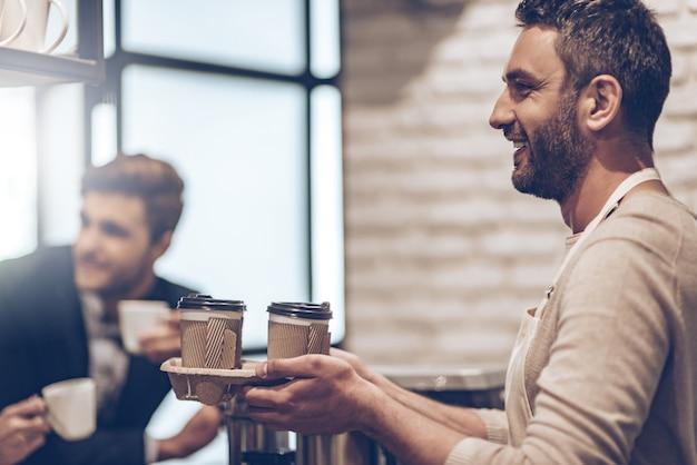 Ваш кофе на вынос! бариста с улыбкой передает кофейные чашки своему клиенту, стоя у барной стойки, вид сбоку