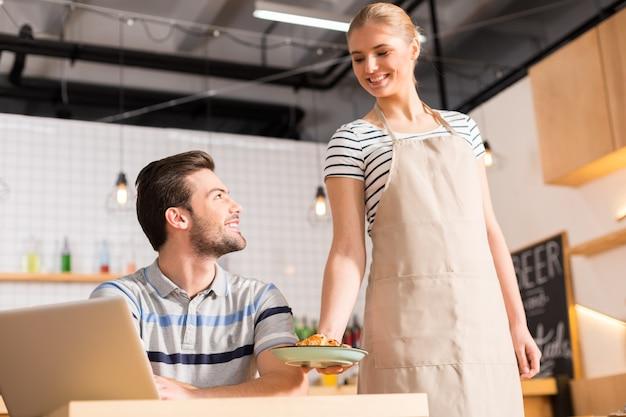 Ваш круассан. обрадованная позитивная дружелюбная женщина смотрит на покупателя и приносит ему заказ, работая официанткой.