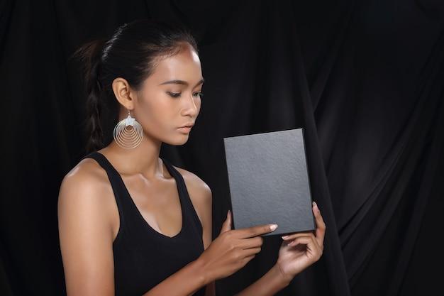 ここにあなたの別のテキスト。空の空白のボードのブラックボックスを保持しているかなり若いアジアのモデルの顔の女性。スタジオ照明暗い背景ポートレート広告エリアの半身コピースペース