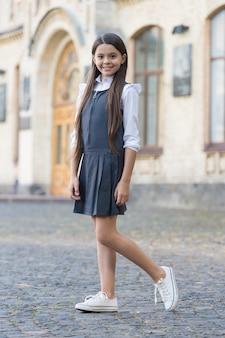Твой наряд в первый день. счастливый ребенок носит равномерное платье на открытом воздухе. снова в школу моды. модный вид маленькой девочки. школьный дресс-код. 1 сентября. осенний тренд. формальное образование.