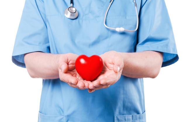 Ваше сердце в надежных руках. крупный план зрелого хирурга-кардиолога, держащего игрушку в форме сердца, стоя изолированную на белом