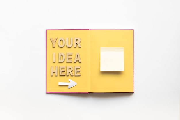 Your idea here text with arrow symbol showing white adhesive notes over book