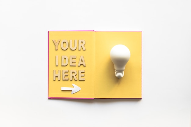Your idea here text with arrow symbol showing white light bulb on book