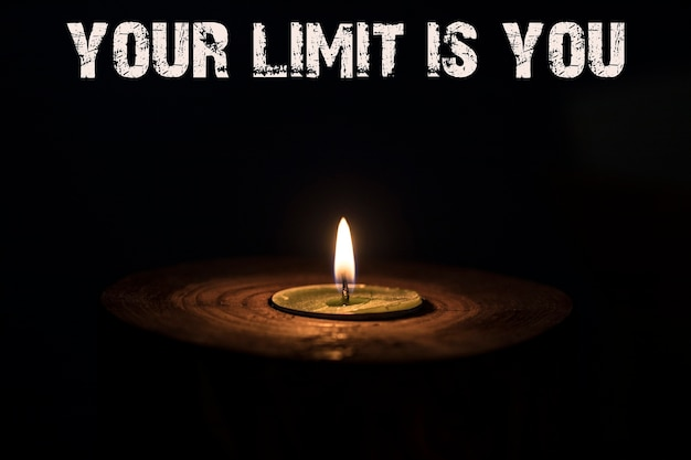 Your limit is you - white candle with dark background - in a wooden candlestick.