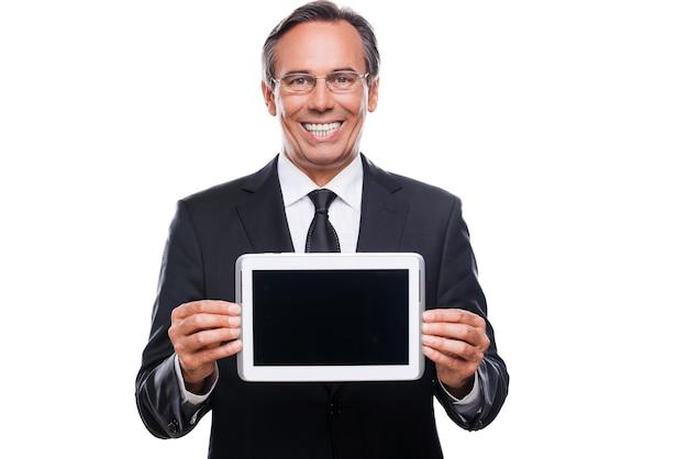 그의 태블릿에 당신의 메시지. 흰색 배경에 격리된 채 디지털 태블릿 모니터를 표시하고 웃고 있는 정장과 안경을 쓴 자신감 있는 성숙한 남자