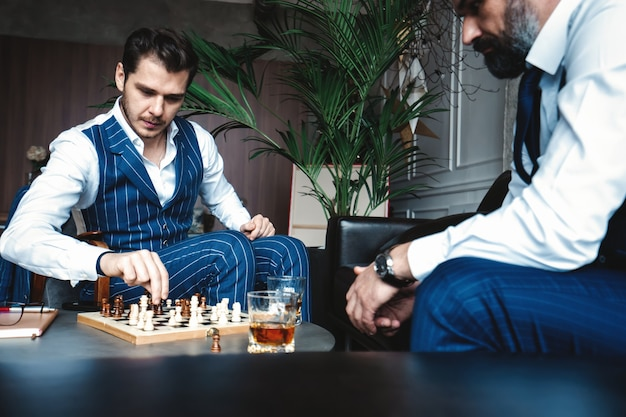 Your move! two young handsome men in full suits playing chess and smiling while sitting indoors.