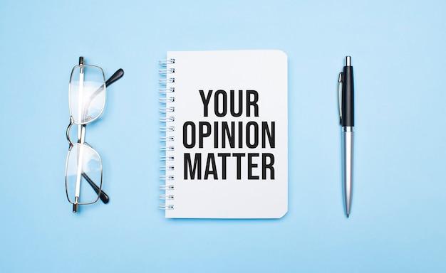 흰색 메모장, 펜 및 파란색 안경에 귀하의 의견 문제 단어