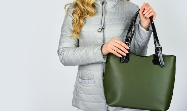 あなたの財布はよく見えるはずです。女性は秋のジャケットを着ます。スタイリッシュな衣装のビジネスレディ。ショッピングとビジネス。フライトクラッチを持つ女の子。エレガントなスタイルを着用してください。ファッションモデルは革のバッグを保持します。コピースペース。