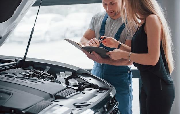 Здесь нужна ваша подпись. результаты ремонта. уверенный мужчина показывает, какие повреждения получила ее машина