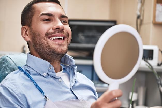 あなたの笑顔は私たちの使命ハンサムな男性患者が座っている彼の美しい笑顔を見ています