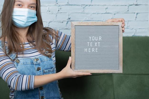Il tuo testo qui poster nelle mani di una ragazza per quanto riguarda la pandemia