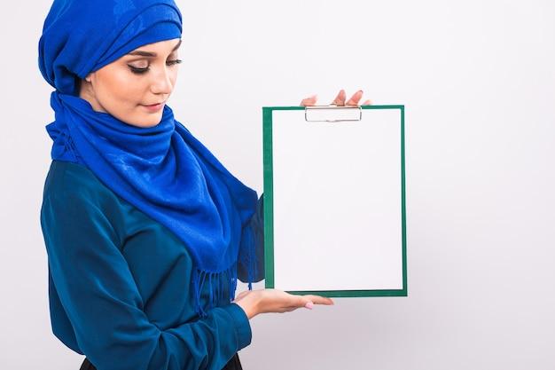Ваш текст здесь. довольно молодая возбужденная арабская женщина, держащая пустую пустую доску. красочный студийный портрет с белым фоном.