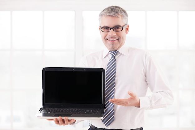 Ваш текст здесь. улыбающийся старший мужчина в рубашке и галстуке держит ноутбук и указывает монитор