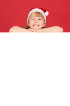 Your text here. vertical studio shot of a little girl smiling lying on top of the white blank placard with copyspace