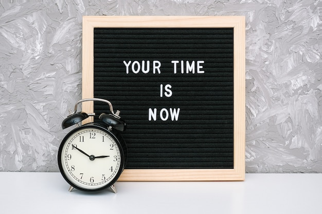 Your time is now, motivational quote on letter board and black alarm clock on table against stone wall.