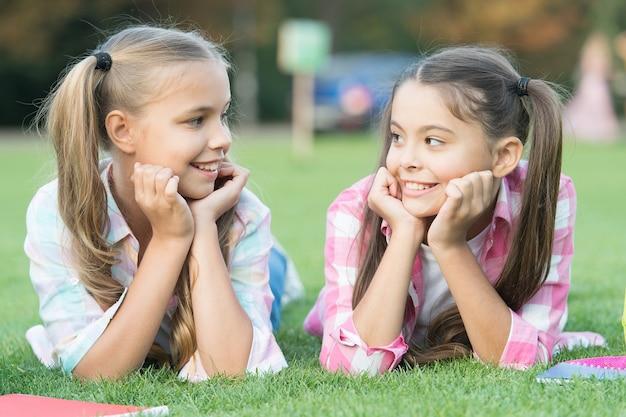 あなたは私のように素晴らしいです。幸せな子供たちは緑の芝生でリラックスします。小さなお子様の美貌。小さな子供たちは幸せな子供時代を楽しんでいます。国際こどもの日。友達を持つことは子供にとって良いことです。