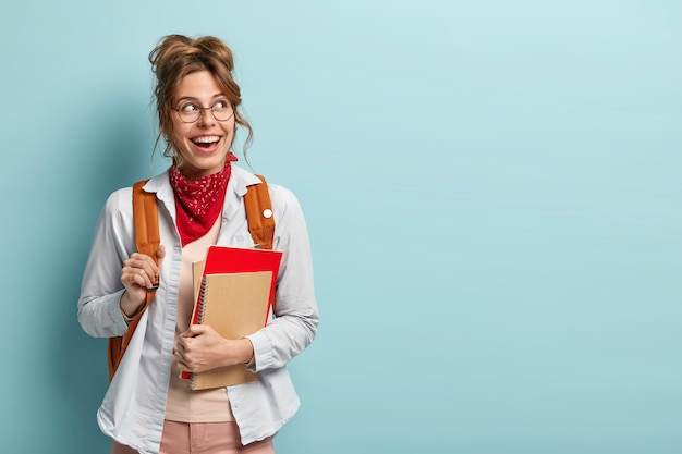 Молодежь и обратно в школу концепции. улыбающаяся студентка ходит на дополнительные занятия, держит блокноты, имеет сумку на спине