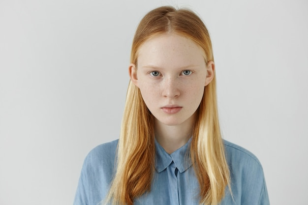 젊음과 아름다움의 개념입니다. 심각한 표정으로 다시 찾고 그녀의 긴 금발 머리를 입고 아름 다운 백인 십 대 소녀의 초상화. 주 근 깨 실내 포즈와 귀여운 젊은 여자