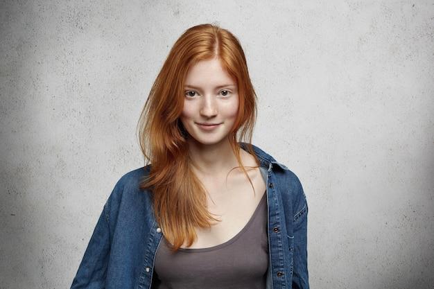 Молодость и счастье. закройте вверх по взгляду красивой кавказской женщины-подростка с длинными рыжими волосами и веснушками, небрежно одетой, стоящей у пустой серой стены.