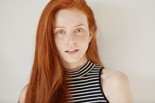 若さとライフスタイルのコンセプトです。長い生姜髪ときれいなそばかすのある肌を持つ魅力的な白人の10代の少女の肖像画を閉じる