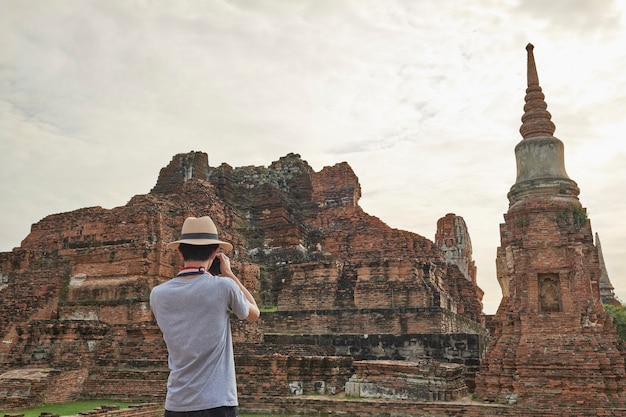 Youth asian travel to photograph ancient temples in ayutthaya, thailand
