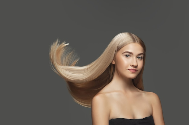 Youth. beautiful model with long smooth, flying blonde hair on dark grey studio background. young caucasian model with well-kept skin and hair blowing on air. concept of salon care, beauty, fashion.