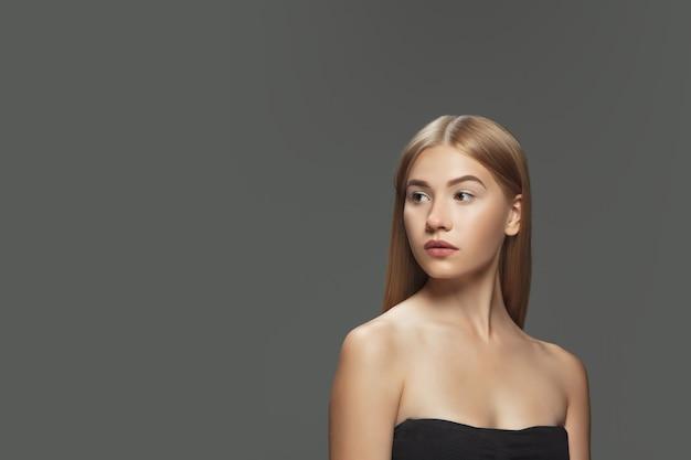 若者。ダークグレーのスタジオの背景に長く滑らかな、飛んでいるブロンドの髪を持つ美しいモデル。手入れの行き届いた肌と髪の毛が空気を吹き込んでいる若い白人モデル。サロンケア、美容、ファッションのコンセプト。