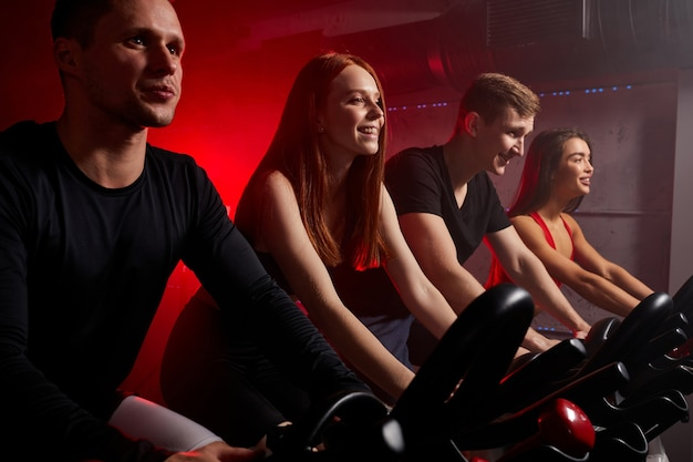 現代のジムでスピニングクラスで自転車に乗って、エアロバイクで運動している若者。エアロバイクでの強い男性と女性のトレーニング