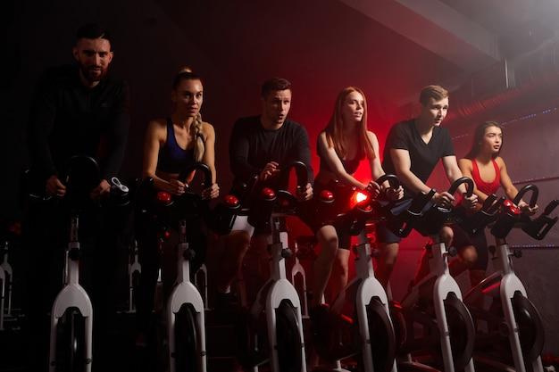 Молодежь катается на велосипеде в классе спиннинга в современном тренажерном зале, тренируется на велотренажере. сильные мужские и женские тренировки на велотренажере