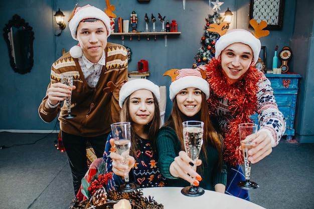 若者はシャンパンとカーニバルの衣装でクリスマスを祝います