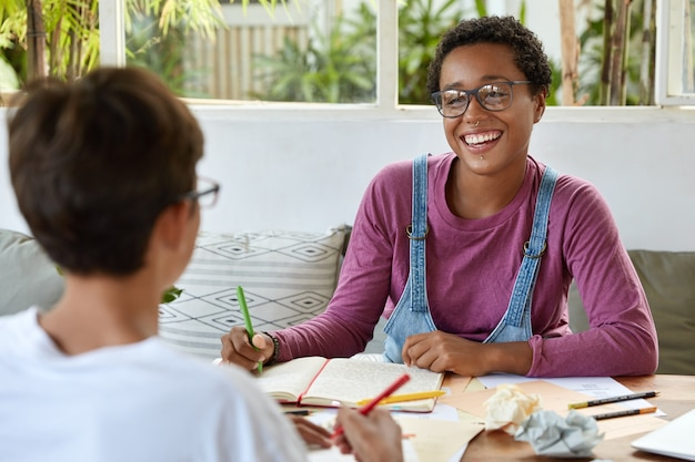Youth and coworking concept. pleased smiling dark skinned lady in spectacles, wears piercing collaborates with her groupmate, makes common task, prepare home assignment, discuss educational issues.