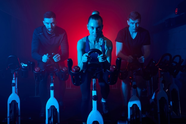 Youth in the gym, exercising their legs doing cardio training, having spinning class at gym in dark neon lighted smoky space
