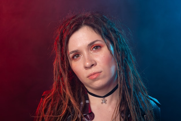 若さ、髪型、モダンなコンセプト-赤と青の光の上にドレッドヘアを持つ若い女性