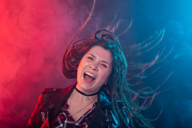 Youth, hairstyle and modern concept - young woman with dreadlocks smiling and having fun over the