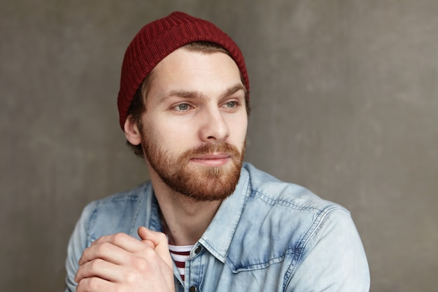 Youth and happiness. close up shot of attractive young european man with beard wearing fashionable hat and denim shirt looking away with joyful facial expression, thinking about something pleasant