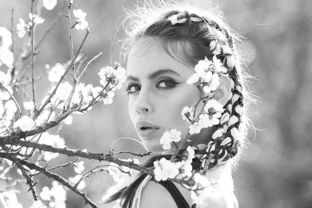 Youth health, freshness concept, people and nature, floral design. black white. beautiful girl in spring park with flowers.