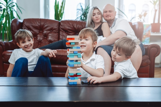 Youth and joyful brother have a good time competing each other and playing jenga game. relaxed domestic lifestyle of family.