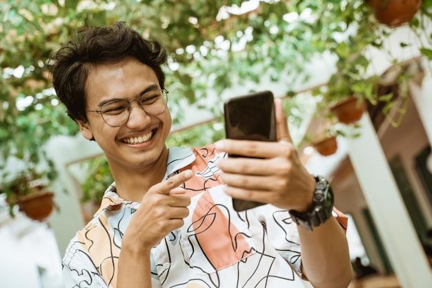 若者は携帯電話を持って笑う