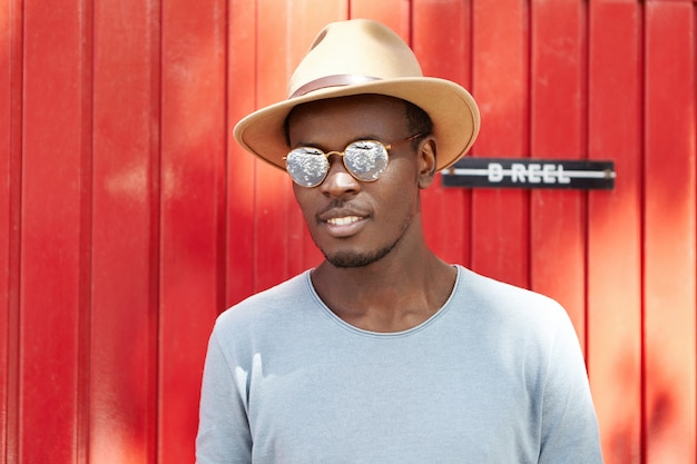 Youth and lifestyle. people and fashion. trendy-looking young afro american man model wearing fashionable round shades and beige hat with brims posing outdoors at red wooden wall on sunny day